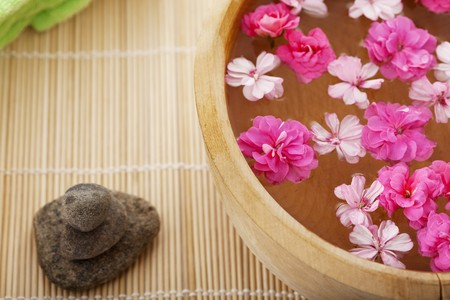Image of spa therapy, flowers in water, on a bamboo mat. photo