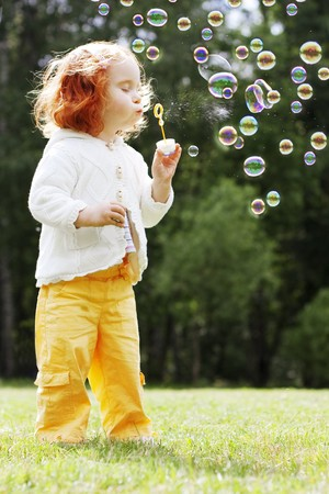 soap bubble: The image of the girl puts the bubbles in the park