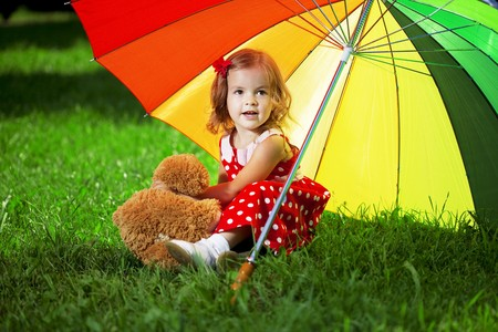 rainbow umbrella: The image of a little girl with a rainbow umbrella in park