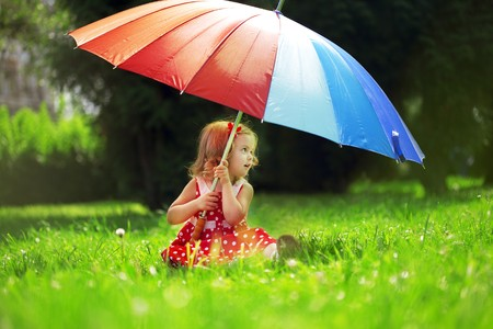 The image of a little girl with a rainbow umbrella in park photo