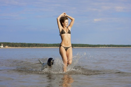Images of beautiful slender girl playing on the beach with a dog photo
