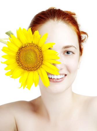 The image of a beautiful smiling girl with a sunflower in the hands