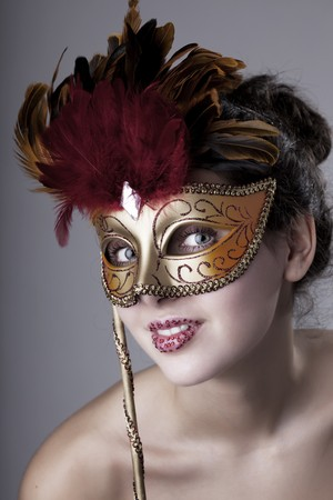The image of a beautiful girl with a carnival mask in the hands photo