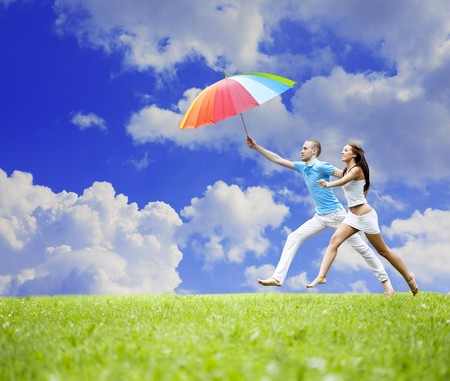 The image of two lovers people jumping with an umbrella in his hand against the sky