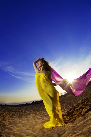 The image of a beautiful girl at the beach growing tissue on a background of the sun. photo