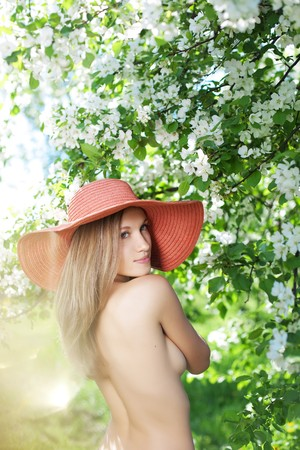 The image of a beautiful half-naked woman among flowering gardens photo