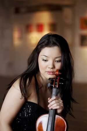 The image of a beautiful asian girl with a violin on the parquet floor photo