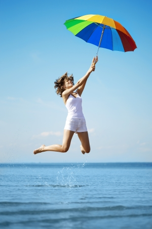 The image of a beautiful girl who jump with a rainbow umbrella Stock Photo