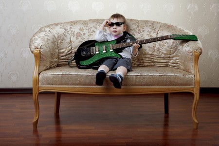 The image of a little boy fashion guitarist sitting on the glamorous couch photo