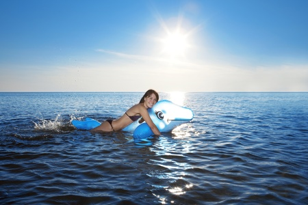 The image of a girl with an inflatable dolphin swims in the sea photo