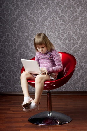 Image of girl sitting in a chair with a laptop photo
