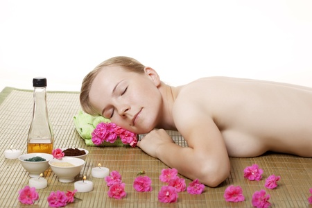 Image of beauty woman getting spa treatment,  laying on bamboo mat. photo