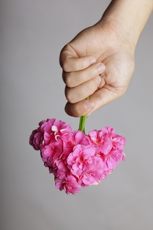 Image of the hand gives a bouquet of flowers in heart shape photo