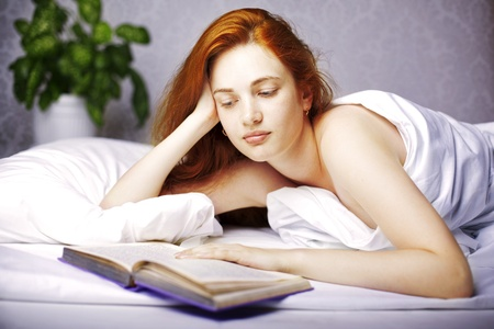 Image of a woman who reads a book in bed photo
