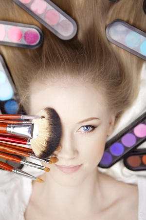 Image of girl stylist makeup artist with brushes and cosmetics photo