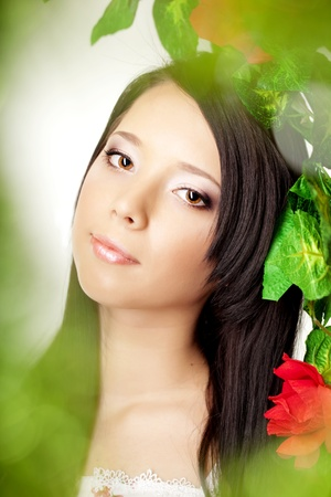 The image of a beautiful girl with bright make-up among the roses photo