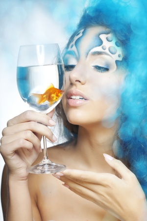 The image of a girl with makeup with a fish in a glass in her hand photo