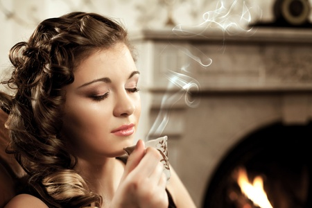 The image of a girl drinking coffee by the fireplace Stock Photo