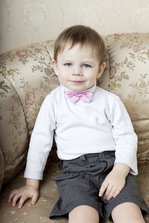 The image of a cute little boy on a background of vintage sofa photo