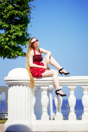 The image of a beautiful girl in the red dress on the beach photo