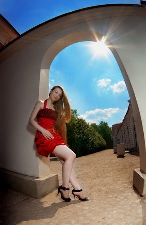 Image of luxury girl in a red dress against the sun photo