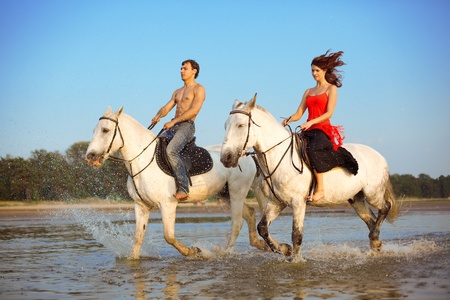 Image of a man and a woman in love with the sea on horseback photo