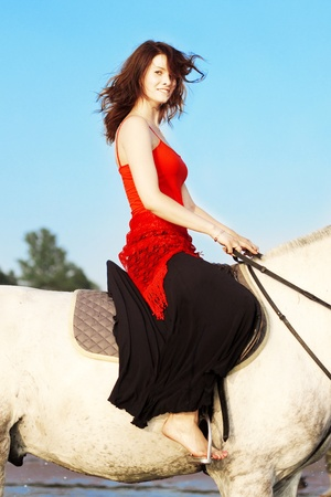 bridle: The image of a girl riding a horse on the background of the sea Stock Photo