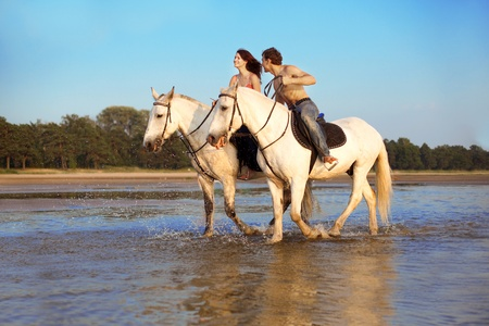 horseback: Image of a man and a woman in love with the sea on horseback Stock Photo