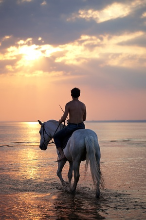 The image of a male riding a horse on the background of the sea photo