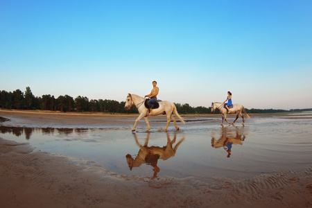 Young couple in the sea on horseback photo