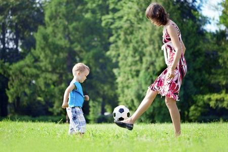 Image of family, mother and son playing ball in the park. photo