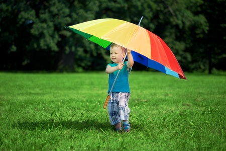 umbrella rain: The image of a little boy with a big rainbow umbrella