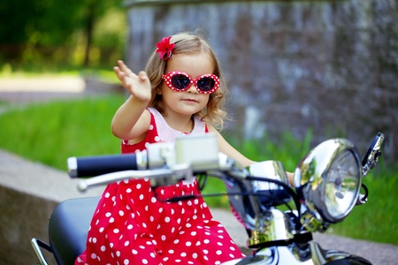 Beautiful little girl in a red dress on a motorcycle Stock Photo