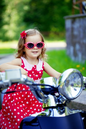 Beautiful little girl in a red dress on a motorcycle Reklamní fotografie