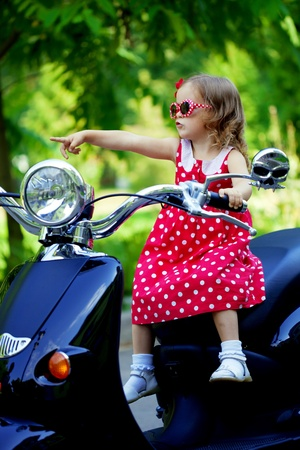 Beautiful little girl in a red dress on a motorcycle Stock Photo - 11527486