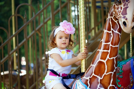 The image of a girl riding on a carousel photo