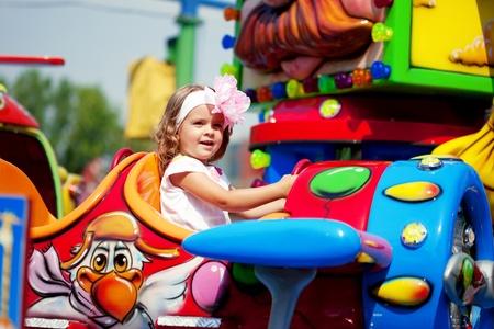 playground ride: The image of a girl riding on a carousel