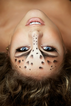 The image of a beautiful girl with an unusual make-up as a leopard photo