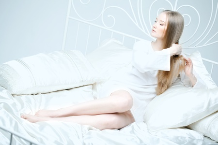The image of a girl combing her hair in bed photo