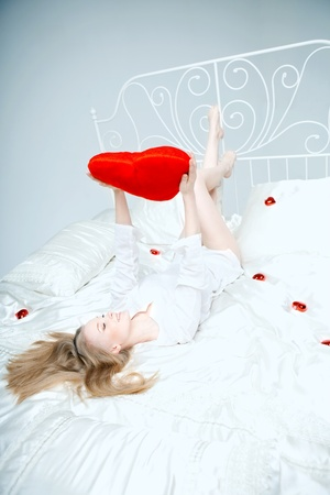 red pillows: The image of a girl lying on the bed with a red heart in her hands