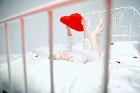 The image of a girl lying on the bed with a red heart in her hands photo