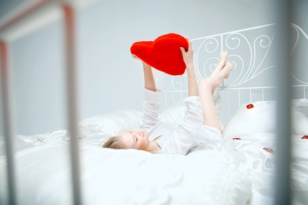 rest day: The image of a girl lying on the bed with a red heart in her hands