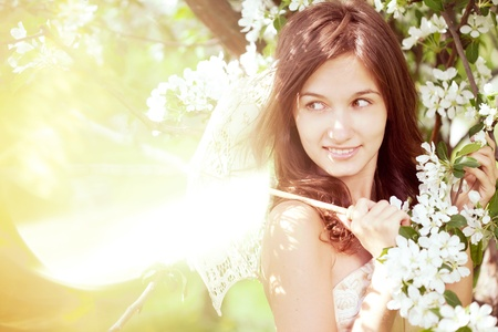The image of a beautiful girl in the lush spring garden photo