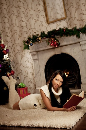 Image of the girl lying near the fireplace and reads a book photo