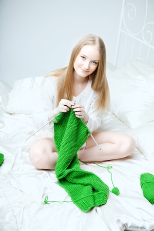 The image of a girl who knits on the needles photo