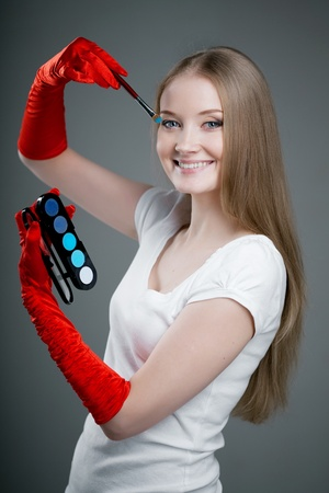 Image of girl in gloves with the professional makeup brush in her hands. photo