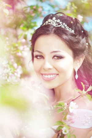 The image of a beautiful bride in a blossoming garden photo