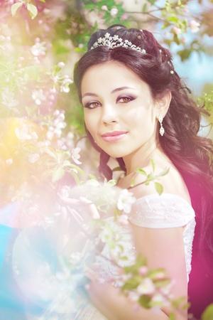 Das Bild einer schönen Braut in einem blühenden Garten Standard-Bild