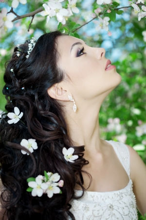 The image of a beautiful bride in a blossoming garden