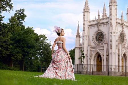 Une femme comme une princesse dans une robe vintage devant le château magique